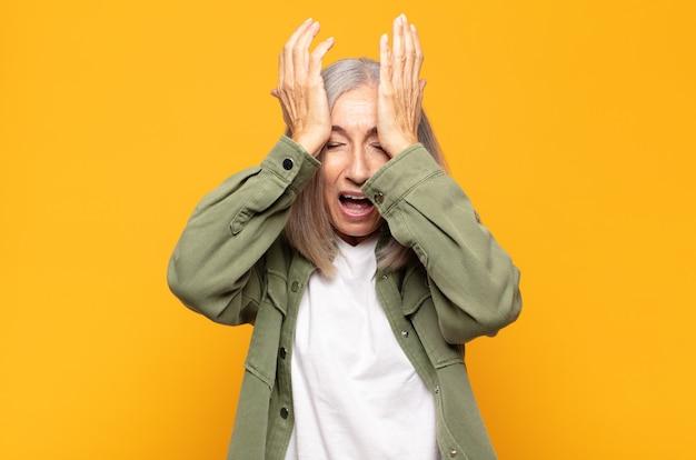 Женщина среднего возраста чувствует стресс и тревогу, депрессию и разочарование из-за головной боли, поднимает обе руки к голове.