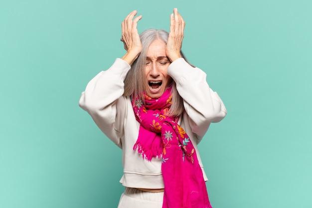 中年の女性は、ストレスと不安を感じ、頭痛で落ち込んで欲求不満を感じ、両手を頭に上げます