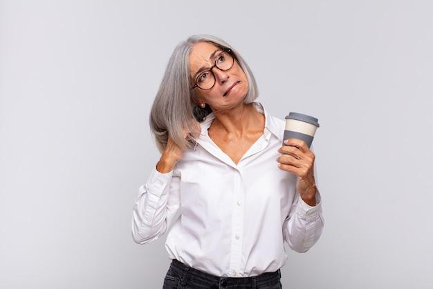 ストレス、不安、疲れ、欲求不満を感じている中年の女性、シャツの首を引っ張って、問題のあるコーヒーのコンセプトに不満を感じている