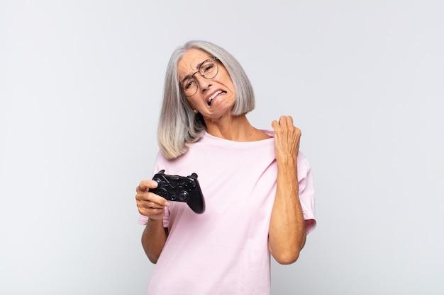 Женщина среднего возраста чувствует стресс, тревогу, усталость и разочарование, тянет рубашку за шею, выглядит расстроенной проблемой. концепция игровой консоли