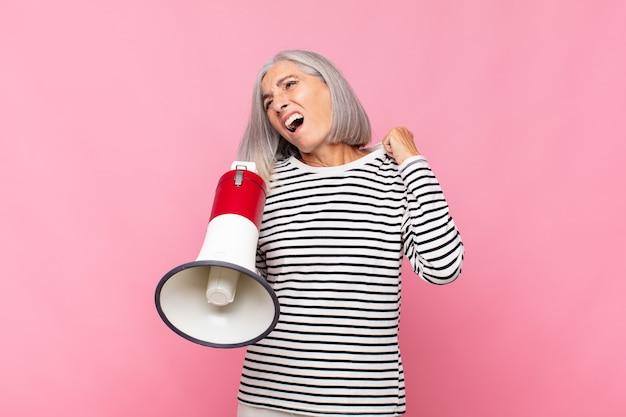 Женщина среднего возраста чувствует стресс, тревогу, усталость и разочарование, дергает за шею рубашки, выглядит расстроенной из-за проблемы с мегафоном