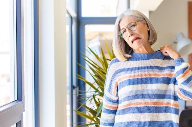 中年の女性は、ストレス、不安、疲れ、欲求不満を感じ、シャツの首を引っ張って、問題で欲求不満に見える