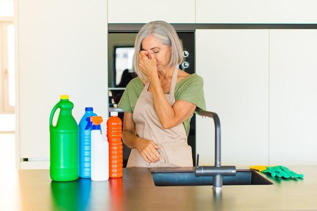 Женщина среднего возраста чувствует стресс, несчастье и разочарование, трогает лоб и страдает от сильной мигрени.