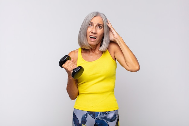 Женщина среднего возраста чувствует стресс, беспокойство, тревогу или страх, с руками за голову, паникует из-за ошибки. фитнес-концепция