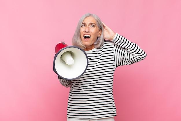 중년 여성이 스트레스, 걱정, 불안 또는 무서움을 느끼고 머리에 손을 얹고 확성기로 실수에 당황합니다.