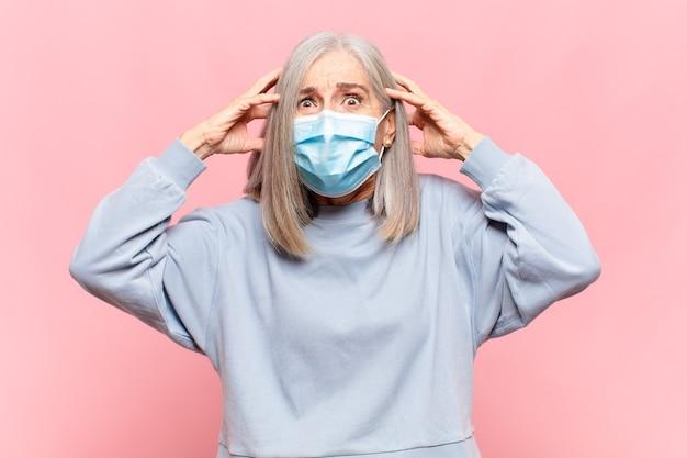 Женщина среднего возраста чувствует стресс, беспокойство, тревогу или страх, с руками за голову, паникует из-за ошибки