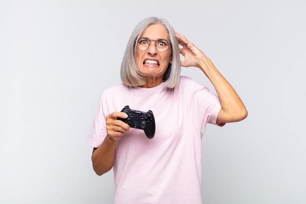 Middle age woman feeling stressed, worried, anxious or scared, with hands on head, panicking at mistake. playing console concept