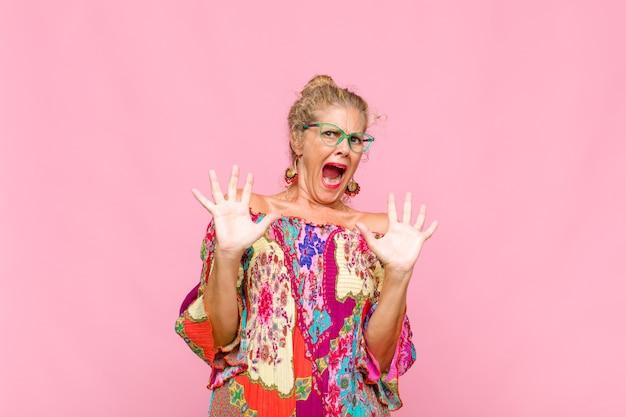 Женщина среднего возраста чувствует себя ошеломленной и напуганной, боится чего-то пугающего, с раскрытыми руками говорит: «держись подальше»