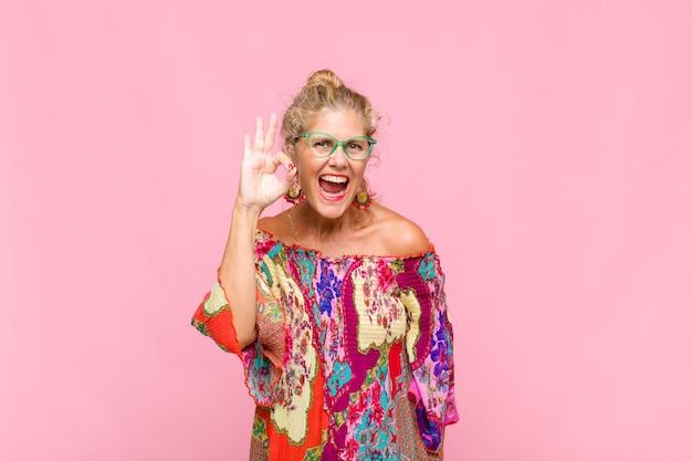 成功と満足を感じ、口を大きく開いて笑顔、手で大丈夫サインを作る中年女性