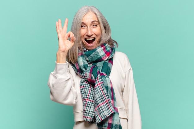 중년 여성이 성공하고 만족감을 느끼고 입을 벌리고 웃고 손으로 괜찮은 기호 만들기