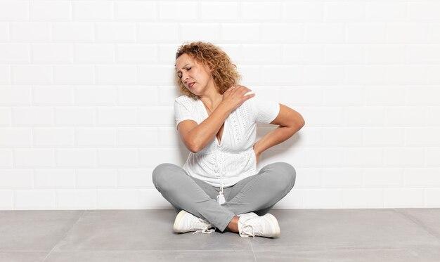 Женщина среднего возраста чувствует усталость, стресс, тревогу, разочарование и депрессию, страдает от боли в спине или шее.