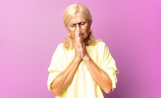 Женщина среднего возраста чувствует беспокойство, надежду и религиозность, верно молится, прижав ладони, умоляя о прощении