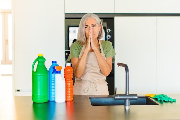 Женщина среднего возраста чувствует беспокойство, надежду и религиозность, верно молится со сжатыми ладонями, умоляет о прощении