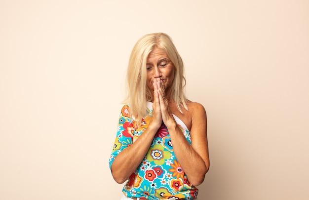 Женщина среднего возраста чувствует беспокойство, надежду и религиозность, верно молится