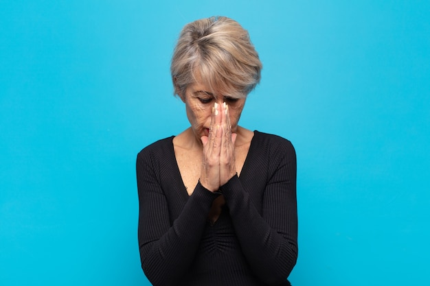 Middle age woman feeling worried, hopeful and religious, praying faithfully with palms pressed, begging forgiveness
