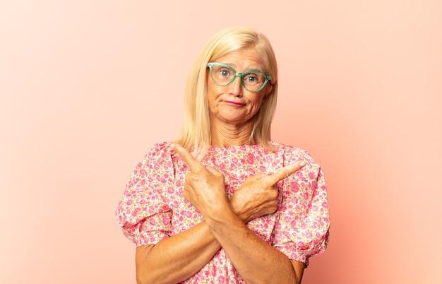 Женщина среднего возраста, обрамляющая или очерчивающая собственную улыбку обеими руками, выглядящая позитивно и счастливой, концепция благополучия