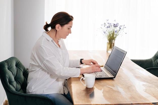 中年女性のフリーランサーは、ラップトップと電話に取り組んでいます