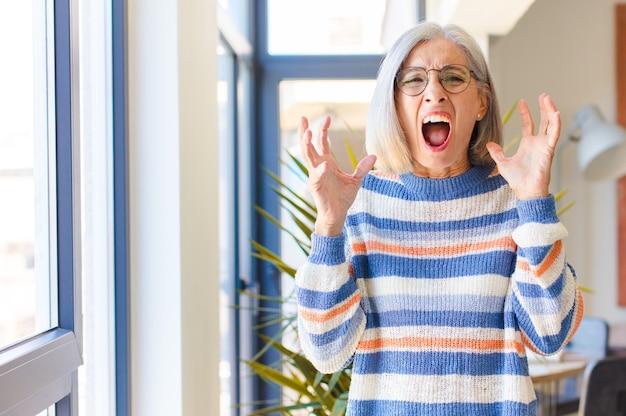 中年の女性が猛烈に叫び、ストレスを感じ、空中に手を上げてイライラしている理由を言って