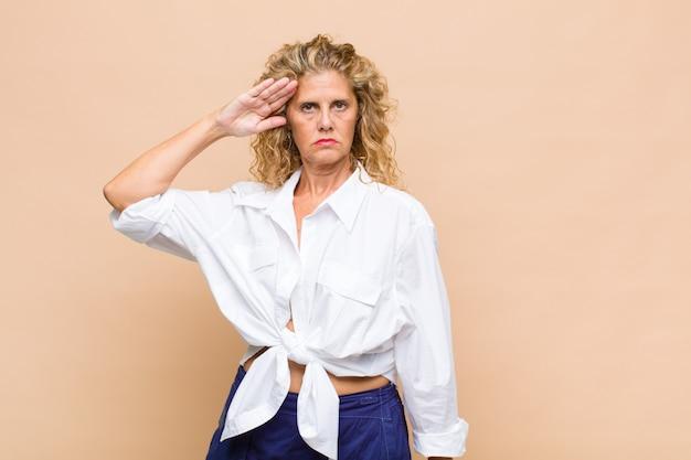 敬礼と愛国心の行為で軍の敬礼で挨拶する中年の女性