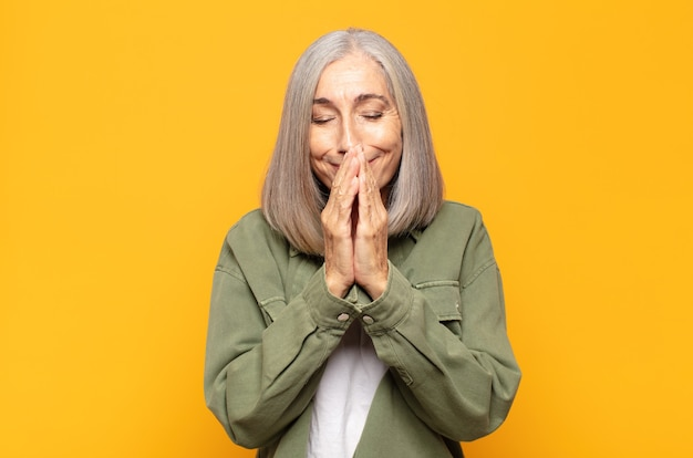 Middle age woman happy and excited, surprised and amazed covering mouth with hands, giggling with a cute expression