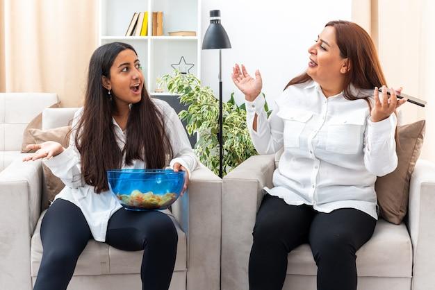 Donna di mezza età e la sua giovane figlia in camicie bianche e pantaloni neri seduti sulle sedie figlia con una ciotola di patatine che litigano con sua madre in soggiorno luminoso