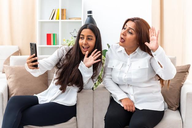 Donna di mezza età e la sua giovane figlia in camicie bianche e pantaloni neri seduti sulle sedie con smartphone con videochiamata felice e positiva che saluta con le mani in soggiorno luminoso