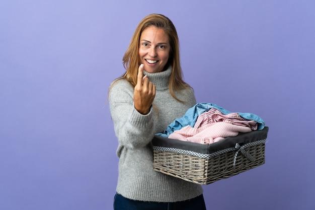 Женщина среднего возраста, держащая корзину с одеждой, изолированная на фиолетовом, делает приближающийся жест