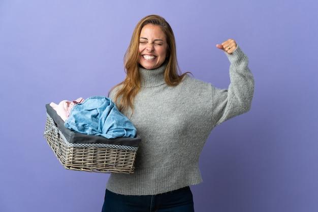 強いジェスチャーをしている紫色の壁に隔離された服のバスケットを保持している中年女性