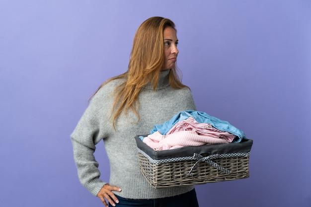 Женщина среднего возраста, держащая корзину с одеждой, изолированная на фиолетовой стене, смотрящая в сторону