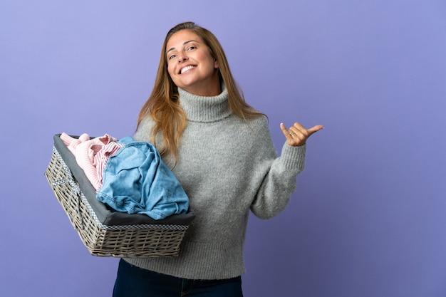 製品を提示する側を指している紫色の壁に隔離された洋服バスケットを保持している中年女性