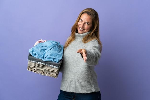 かなり閉じるために握手する紫色の壁に隔離された服のバスケットを保持している中年の女性