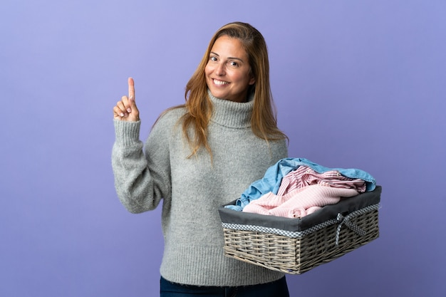 紫色の壁に隔離された服のバスケットを持っている中年の女性は、最高の兆候を示して指を持ち上げます