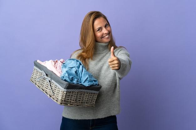何か良いことが起こったので、親指を立てて紫色の壁に隔離された洋服バスケットを持っている中年女性
