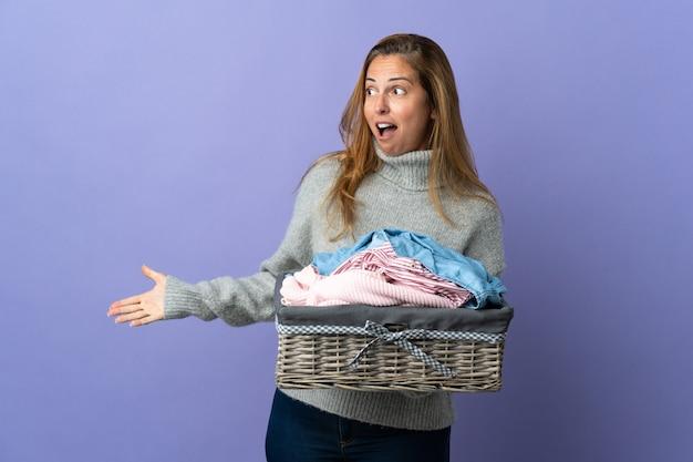 側面を見ながら驚きの表情で紫に分離された洋服バスケットを保持している中年女性