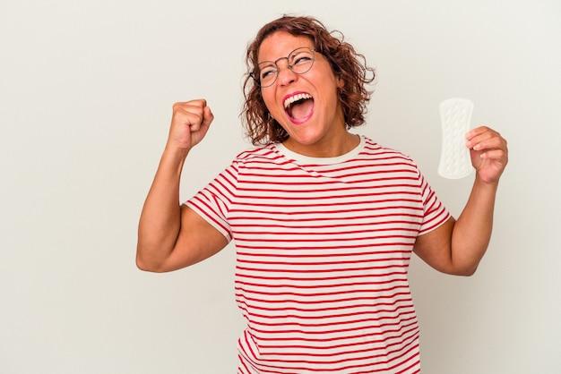 勝利、勝者の概念の後に拳を上げる白い背景で隔離の湿布を保持している中年の女性。