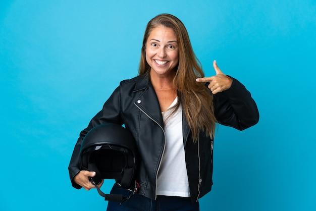 親指を立てるジェスチャーを与える孤立したオートバイのヘルメットを保持している中年女性