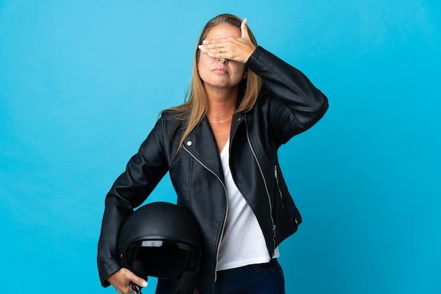 手で目を覆っている青で隔離のオートバイのヘルメットを保持している中年女性。何かを見たくない