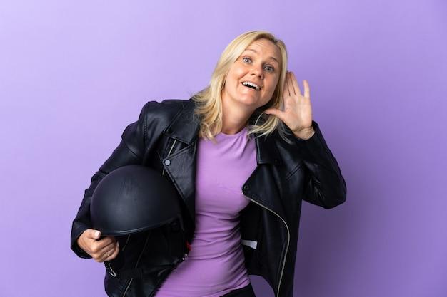 耳に手を置いて何かを聞いて紫色で隔離のオートバイのヘルメットを保持している中年女性