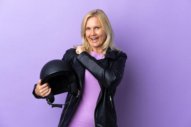 승리를 축하하는 보라색 벽에 고립 된 오토바이 헬멧을 들고 중년 여자