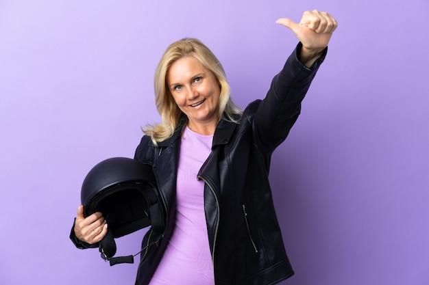 제스처를 엄지 손가락을주는 보라색 벽에 고립 된 오토바이 헬멧을 들고 중년 여자