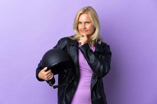 찾는 동안 의심을 갖는 보라색 벽에 고립 된 오토바이 헬멧을 들고 중년 여자