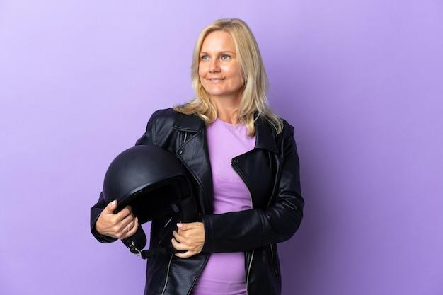 보라색 벽에 고립 된 오토바이 헬멧을 들고 중년 여자가 측면을보고 웃