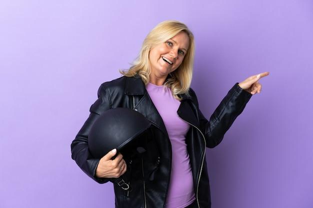 측면에 손가락을 가리키는 보라색 벽에 고립 된 오토바이 헬멧을 들고 제품을 제시하는 중년 여성