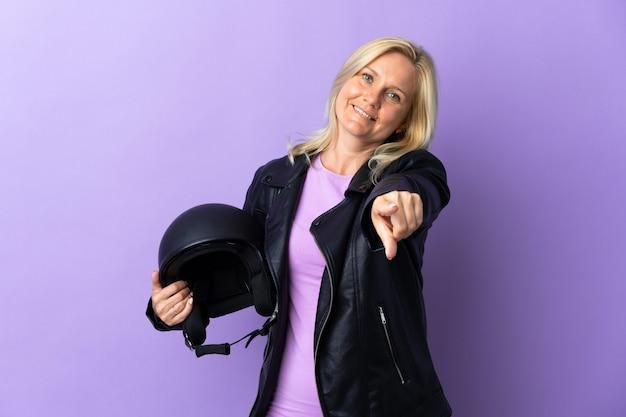 幸せな表情で正面を向いて紫色の壁に分離されたオートバイのヘルメットを保持している中年女性