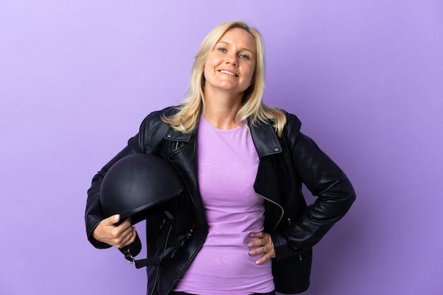 오토바이 헬멧을 들고 중년 여자 엉덩이에 팔을 포즈와 미소 보라색 벽에 고립