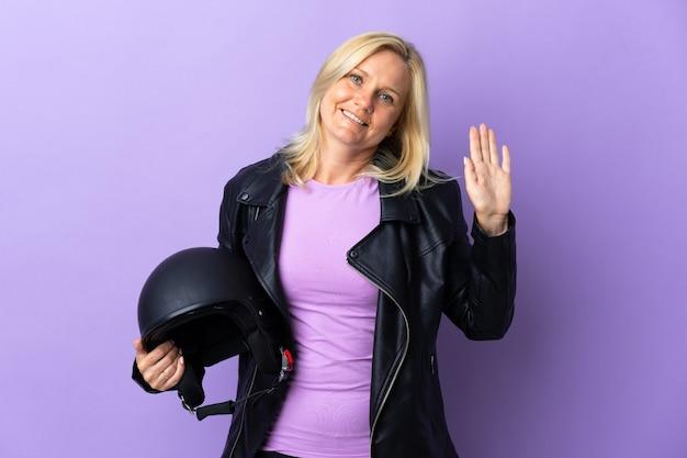 幸せな表情で手で敬礼する紫色の壁に分離されたオートバイのヘルメットを保持している中年女性