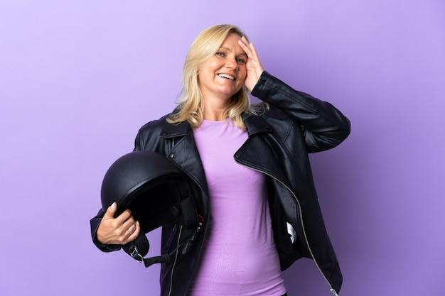 많은 미소 보라색 벽에 고립 된 오토바이 헬멧을 들고 중년 여자