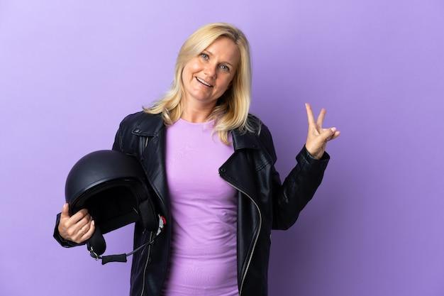 웃 고 승리 기호를 보여주는 보라색 벽에 고립 된 오토바이 헬멧을 들고 중 년 여자