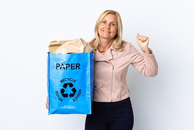 勝者の位置での勝利を祝う白で隔離のリサイクルする紙でいっぱいのリサイクルバッグを保持している中年の女性