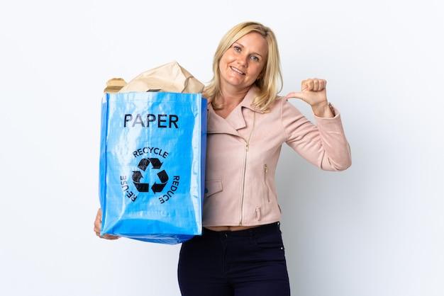 親指を立てるジェスチャーを与える白で隔離のリサイクルする紙でいっぱいのリサイクルバッグを保持している中年女性